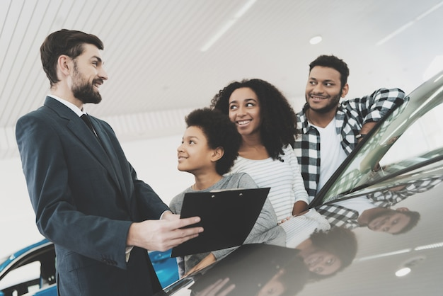 Sallesman showing a car to a family
