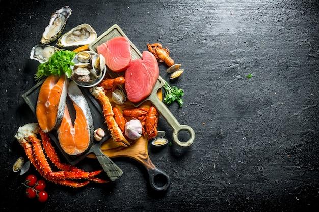 Стейки из лосося и тунца с различными морепродуктами и зеленью.