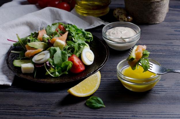 ダークウッドのテーブルのダークプレートに焦点を当てたサーモンと野菜のサラダ