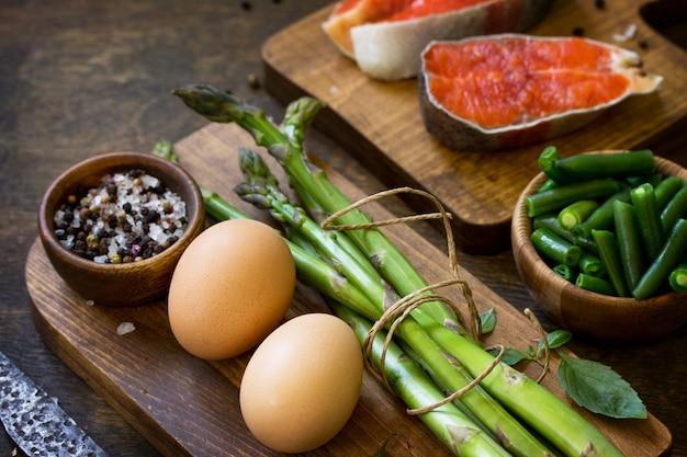 木製の背景にサーモンアスパラガスと卵