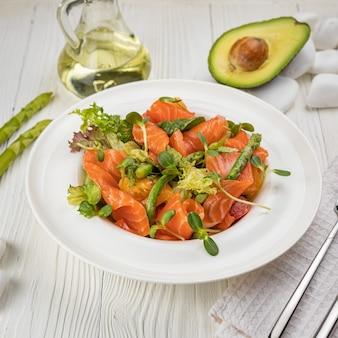 Салат из лосося, спаржи и зелени на белой тарелке и белом столе