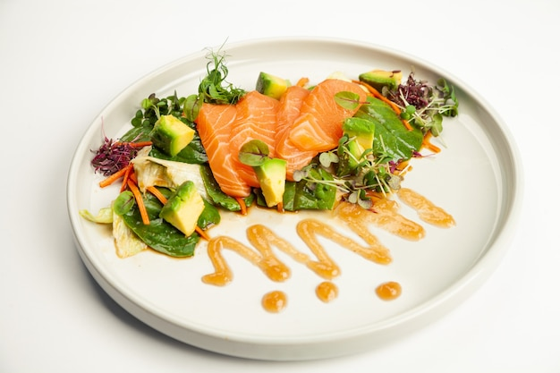 Salmon and avocado salad in tamarind sauce on a plate.