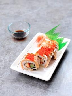 Суши-ролл с лососем, крабовая палочка, огурец и жареный лосось с тобико. подается на белой прямоугольной тарелке.