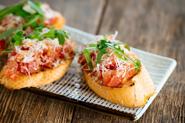 Salmon bruschettas with grated cheese and arugula