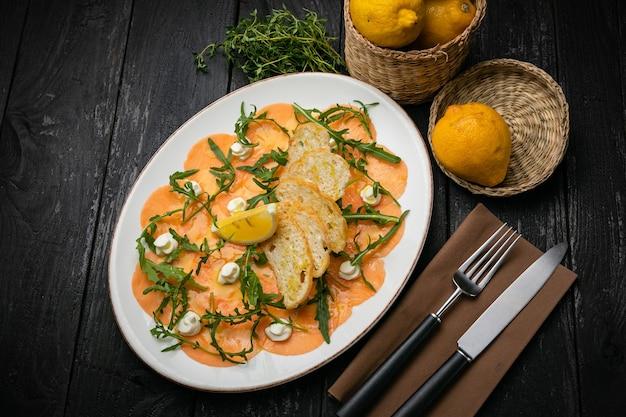Карпаччо из лосося на тарелке с лимонами, рукколой, козьим сыром и гренками