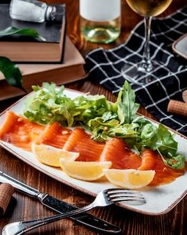 Карпаччо из лосося с лимоном на столе