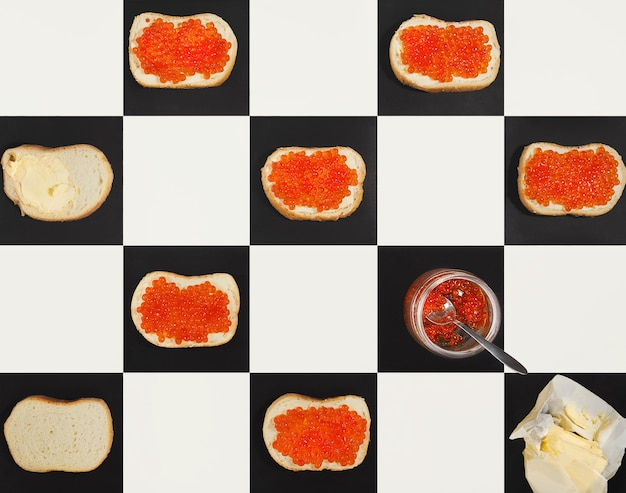 チェスのボードにパターンを形成する瓶の中のサーモンキャビアカナッペ、バター、イクラ