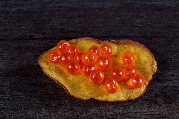 Salmon caviar with potato chips on a black wood