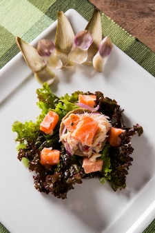 Salmon ceviche, crab and salad with artichoke