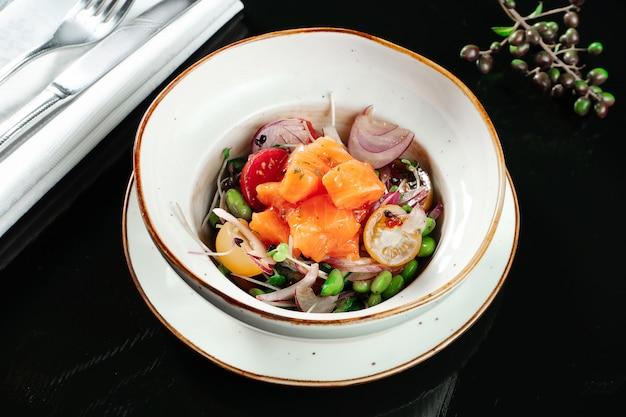 Салат из лосося севиче с помидорами черри, листьями салата, зеленой фасолью, луком и помидорами черри. салат из свежих морепродуктов. здоровая пища на обед. закрыть