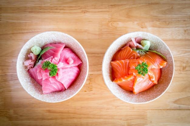 サーモンドンとマグロまたはマグロのドンスライスしたサーモンとマグロまたはマグロを日本米の上に乗せたもの木製のテーブルの白いボウルにわさびと生姜のピクルスを添えて。