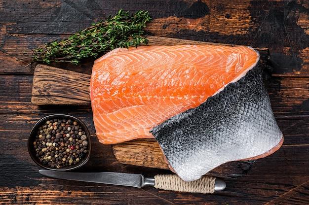 Филе лосося рыбы на деревянной доске с зеленью и солью. темный деревянный фон. вид сверху.