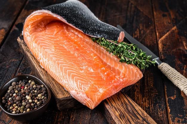 Филе лосося рыбы на деревянной доске с зеленью и солью
