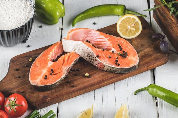 Филе лосося на деревянной доске с лимоном и помидорами с зеленым перцем чили