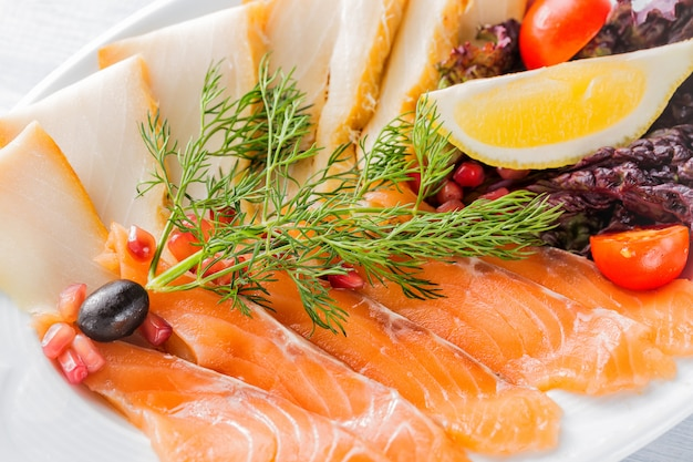 Salmon fillet pieces, sturgeon pieces served with lemon, black olives, herbs, cherry tomato and pomegranate seeds on white plate