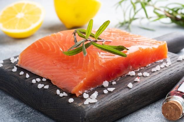 연어 필렛, 나무도 마 보드에 붉은 소금에 절인 생선. 레몬, 로즈마리 향신료.