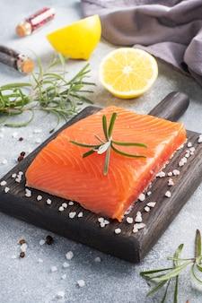 サーモンの切り身、木製のまな板に赤い塩漬けの魚。レモン、ローズマリースパイス。
