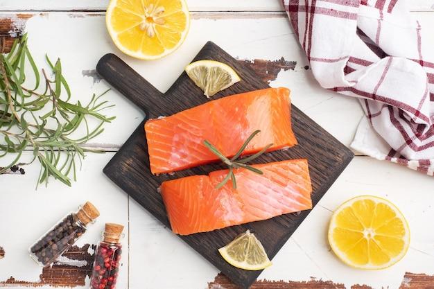 サーモンの切り身、木製のまな板に赤い塩漬けの魚。