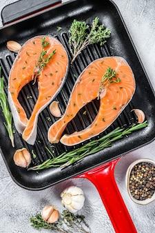 Стейк из филе лосося на сковороде. сырая свежая рыба. белый фон. вид сверху.