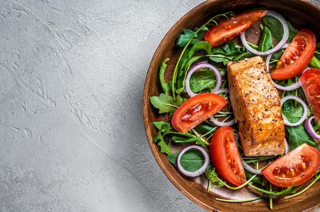 나무 접시에 녹색 잎 arugula, 아보카도, 토마토와 연어 필렛 스테이크 샐러드. 흰색 배경. 평면도. 공간을 복사하십시오.