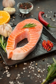 暗い背景にハーブ、スパイス、野菜と鮭の切り身。料理のコンセプトです。料理の背景。食品の背景。健康食品のバランス。テーブル背景メニュー。コピースペース。