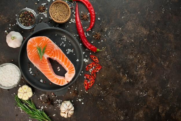 어두운 배경에 향기로운 허브, 향신료, 야채를 넣은 연어 필레. 요리 개념입니다. 요리 배경입니다. 음식 배경입니다. 건강한 음식 균형. 테이블 배경 메뉴입니다. 공간을 복사합니다.