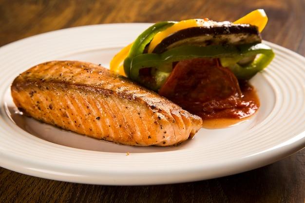Филе лосося с овощной смесью на деревянной поверхности