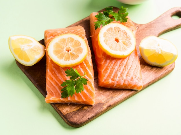Salmon fillet on wooden board with lemon slices