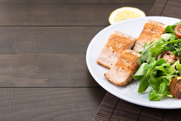 Филе лосося на белом блюде на темном деревянном столе с copyspace.
