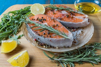Salmon fish on a plate with spices, olive oil and lemon before cooking, vertical.