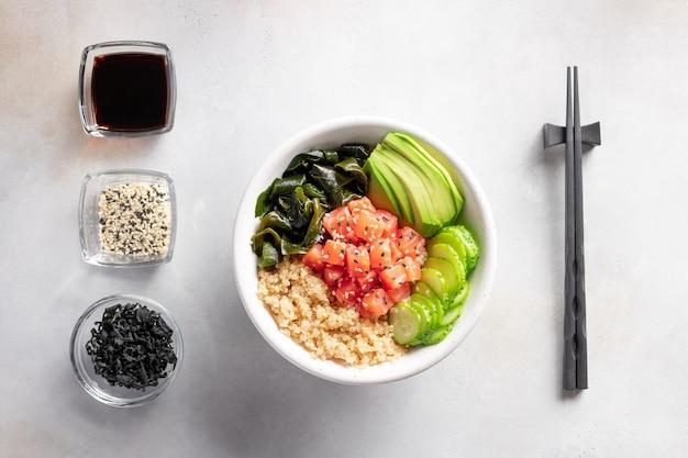 Salmon fish poke bowl with avocado, quinoa, wakame seaweed