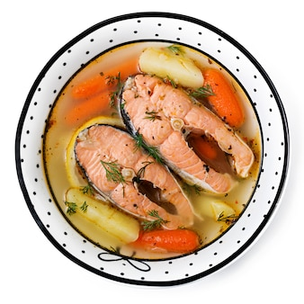 Salmon fish soup with vegetables in bowl. .