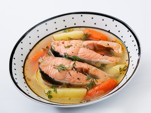 Salmon fish soup with vegetables in bowl.
