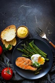 サーモンフィッシュステーキのアスパラガスポーチドエッグ焼きヘルシーフードトップビューフラットレイ