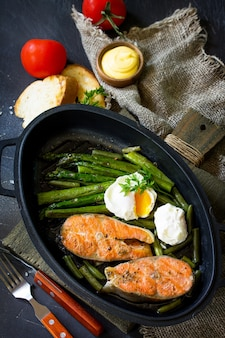 素朴な石のテーブルのフライパンでアスパラガスのポーチドエッグをグリルしたサーモンフィッシュステーキ