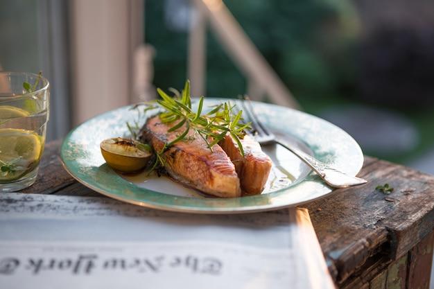 Стейк из лосося на гриле со стаканом воды, ужин. здоровая пища. вид сверху вкусные жареные приправы филе лосося на фоне естественного сада.