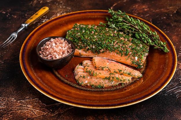 Лосось gravlax, запеченный с укропом и розовой солью на деревенской тарелке. темный фон. вид сверху.