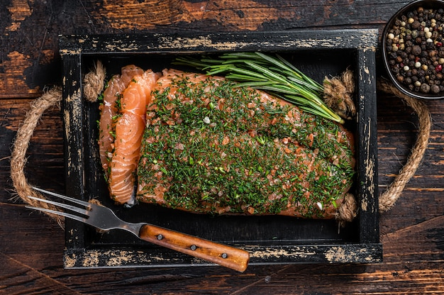 Лосось gravlax, запеченный с укропом и солью на деревянном подносе. темный деревянный фон. вид сверху.