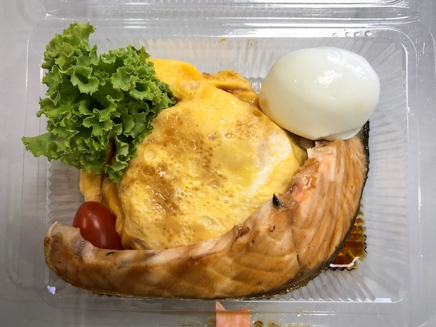 Salmon grilled with rice in egg omelette in the food container on the table