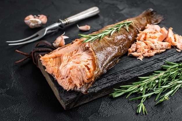 연어 뜨거운 훈제, 송어 생선 고기. 검은 배경. 평면도.