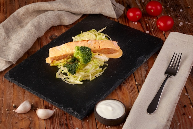 Лосось в сливочном соусе с брокколи, деревянный фон