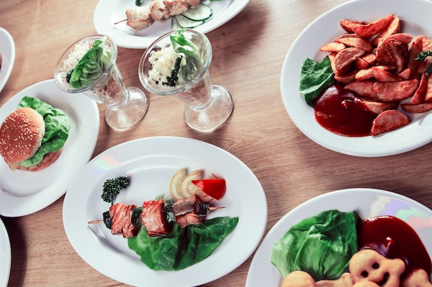 Шашлык из лосося на деревянных шпажках со свежими овощами. посуда для пикника