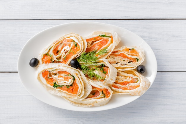 Salmon lavash rolls with dill, cheese and black olives on white plate and wooden table