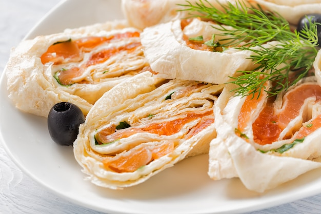 Salmon lavash rolls with dill, cheese and black olives on white plate