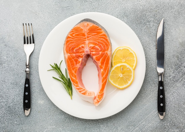 Salmon and lemon on plate flat lay