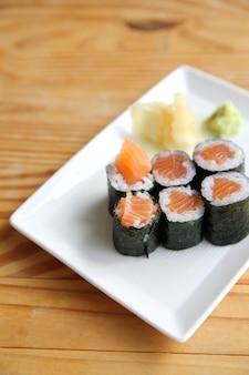 Маки суши с лососем на фоне дерева