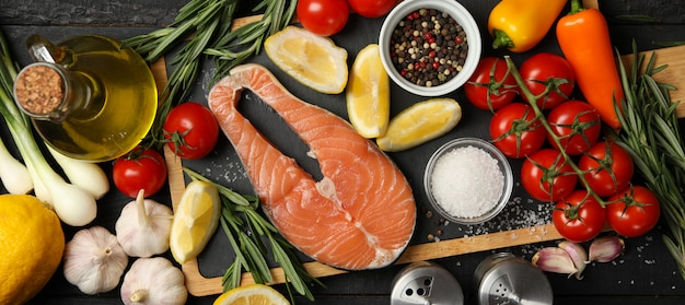 Salmon meat and spices on wooden background