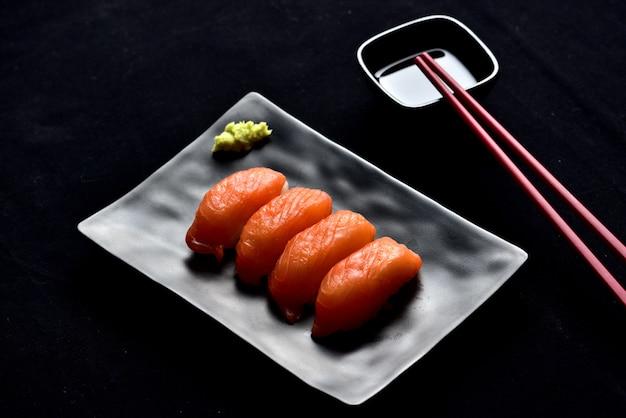 Salmon nigiri sushi and wasabi sauce with chopsticks on black valvet.