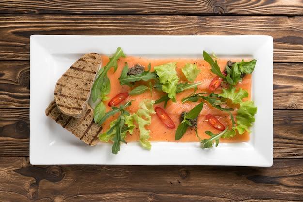 연어 또는 송어 카르 파치 오와 arugula, 핫 칠리 페퍼, 양상추, 바질, 구운 ciabatta가 나무 식탁에있는 흰색 세라믹 접시에 담겨 있습니다. 평면도.