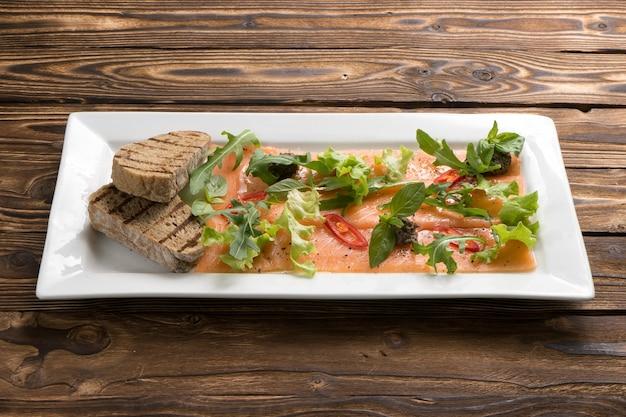 연어 또는 송어 카르 파치 오와 arugula, 핫 칠리 페퍼, 양상추, 바질, 구운 ciabatta가 나무 식탁에있는 흰색 세라믹 접시에 담겨 있습니다.